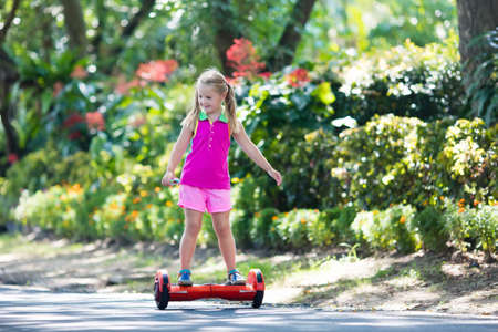 Child on hover board. Kids riding scooter in summer park. Balance board for children. Electric self balancing scooter on city street. Girl learning to ride hoverboard. Modern gadgets for school kid. Stock Photo - 85236134