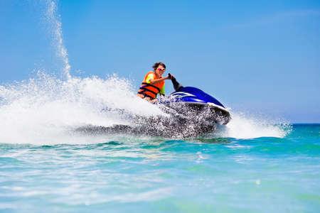 Tiener leeftijd jongen skiën op water scooter. Jonge man op persoonlijke watercraft in tropische zee. Actieve zomervakantie voor schoolkind. Sport en oceaanactiviteiten op strandvakantie. Stockfoto
