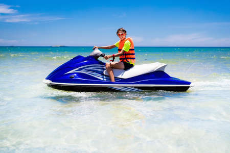 Teen age boy skiing on water scooter. Young man on personal watercraft in tropical sea. Active summer vacation for school child. Sport and ocean activity on beach holiday.
