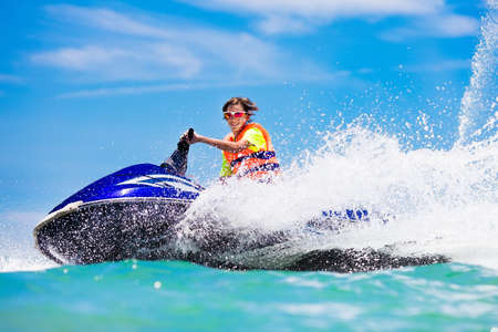 Teenager on water scooter. Teen age boy skiing. Young man on personal watercraft in tropical sea. Active summer vacation for school child. Sport and ocean activity on beach holiday.