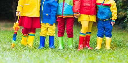 Enfants dans des bottes de pluie. Groupe d'enfants de la maternelle dans des bottes en caoutchouc colorées et des vestes d'automne. Chaussures pour chutes de pluie. Usure des pieds pour enfant et bébé. Tout-petit dans les poissons. Gumboots arc-en-ciel. Mode enfantine Banque d'images - 85166302