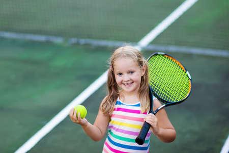 Kind speelt tennis op buitenhof. Meisje met tennisracket en bal in sportclub. Actieve oefening voor kinderen. Zomeractiviteiten voor kinderen. Opleiding voor jong kind. Kind leren spelen.
