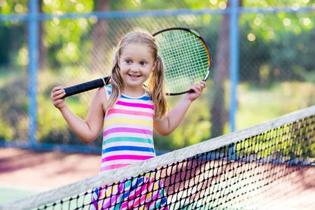 屋外コートでテニスの子。テニス ラケット、スポーツ クラブでボールを持つ少女。子供のためのアクティブな運動。子供のための夏の活動。若い子