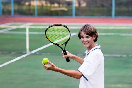 Ragazzo, gioco, tennis, esterno, corte. Adolescente con racchetta da tennis e palla nel club sportivo. Esercizio attivo per i bambini. Attività estive per i bambini. Formazione per un ragazzino. Bambini che imparano a giocare. Archivio Fotografico - 85333106