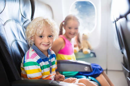 Child in airplane. Kids sit in air plane window seat. Flight entertainment for kid. Traveling with young children. Kids fly and travel. Family summer vacation. Girl and boy with toy in airplane. Archivio Fotografico