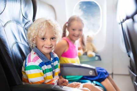 Kind in vliegtuig. Kinderen zitten in het vliegtuig raam stoel. Vlucht entertainment voor een kind. Reizen met jonge kinderen. Kinderen vliegen en reizen. Familie zomervakantie. Meisje en jongen met speelgoed in vliegtuig.