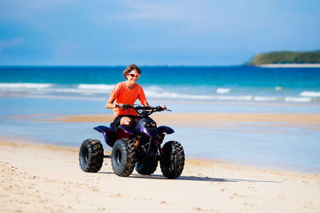Teenager riding quad bike on tropical beach. Active teen age boy on quadricycle. All-terrain vehicle ride. Motor cross sports on ocean sand dune. Off road race at sea shore. Summer vacation activity. Stock Photo