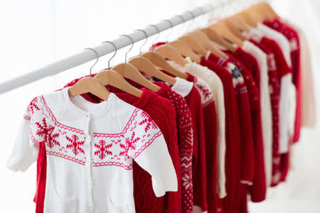 Clothes rack with red Christmas knit wear. Wardrobe with knitted winter cardigan and dress. Xmas clothing collection. Christmas gifts shopping. Winter sale for children wear. Kids clothing shop. Reklamní fotografie - 85410905