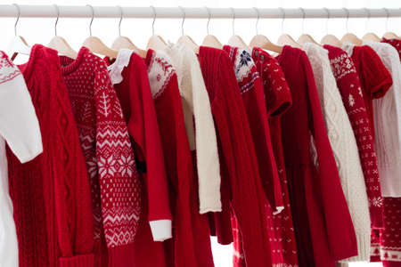 Clothes rack with red Christmas knit wear. Wardrobe with knitted winter jumper and dress. Xmas clothing collection. Christmas gifts shopping. Winter sale for children wear. Kids clothing shop. Reklamní fotografie