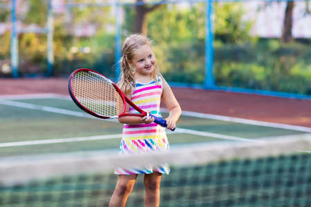 Child playing tennis on outdoor court. Little girl with tennis racket and ball in sport club. Active exercise for kids. Summer activities for children. Training for young kid. Child learning to play. Stock Photo - 85410912