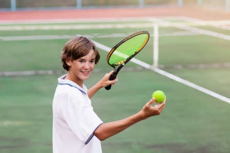 Boy playing tennis on outdoor court. Teenager with tennis racket and ball in sport club. Active exercise for kids. Summer activities for children. Training for young kid. Child learning to play. Imagens