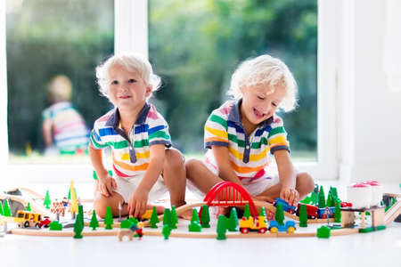 Kids play with toy train railway. Children playing with wooden trains. Toys for little boy. Two brothers build rail road and blocks at home or daycare, preschool. Kindergarten educational games.