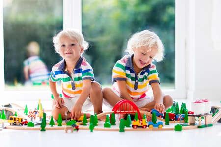 Kinder spielen mit Spielzeugbahn. Kinder spielen mit Holzbahnen. Spielzeug für kleinen Jungen. Zwei Brüder bauen Schienenstraße und Blöcke zu Hause oder Kindertagesstätte, Vorschule. Kindergarten pädagogische Spiele. Standard-Bild - 85357570