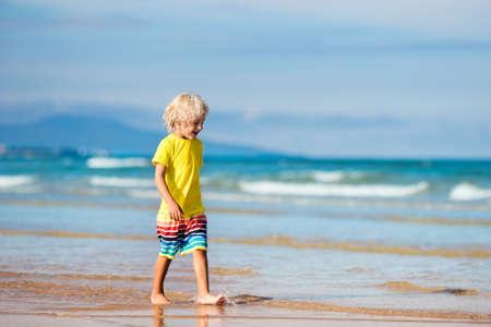 美しいビーチでの子。実行してジャンプ海で海岸の小さな男の子。子供と一緒に海の休暇。子どもたちは、夏のビーチで遊ぶ。水の楽しみ。子供た 写真素材