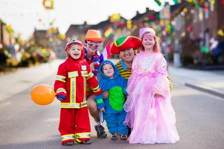 Crianças e pais no Halloween gostosuras ou travessuras. Família em trajes de Halloween com sacos de doces andando na rua decorada doces ou travessuras. Bebê e pré-escola comemorando o carnaval. Fantasia de criança.