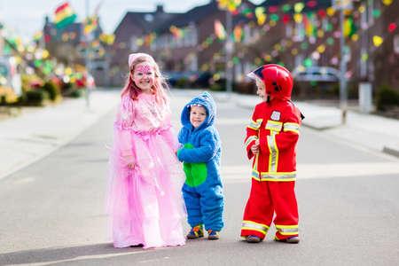 Kinderen op Halloween trick of treat. Kinderen in Halloween kostuums met snoepzakken lopen in een versierde stadswijk of behandelen. Baby en kleuter die carnaval kostuum dragen.