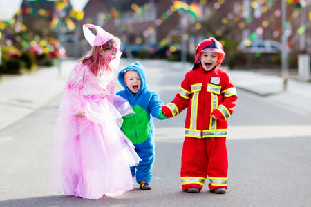 Kids on Halloween trick or treat. Children in Halloween costumes with candy bags walking in decorated city neighborhood trick or treating. Baby and preschooler celebrating carnival wearing costume.