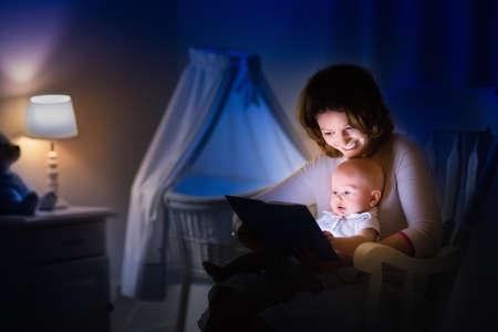Moeder en baby het lezen van een boek in een donkere kamer moeder