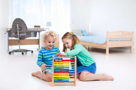 Children playing with wooden abacus. Kids learn to count with educational preschool toy. Wooden toys for kindergarten kid. Child learning math. Boy and girl counting. School student room with desk.