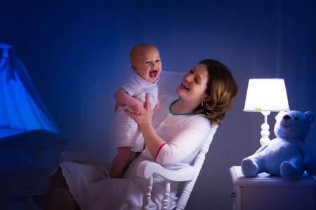 Mutter und Baby lesen ein Buch im dunklen Schlafzimmer. Mama und Kind lesen Bücher vor dem Schlafengehen. Familie am Abend. Kinderzimmer Interieur mit Nachtlampe und Waschbecken. Elternteil Säugling neben Krippe. Standard-Bild - 85704777