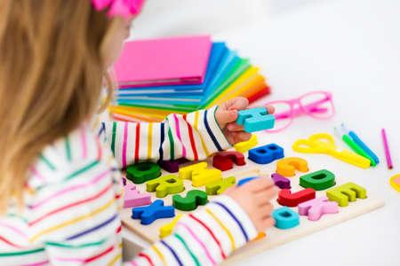 Kind dat thuiswerk voor school doet bij wit bureau. Houten educatieve abc speelgoed puzzel voor kinderen. Gelukkig terug naar school student. Kid leren alfabet letters. Meisje met schoolbenodigdheden en boeken.