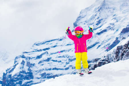 Child skiing in mountains. Active toddler kid with safety helmet, goggles and poles. Ski race for young children. Winter sport for family. Kids ski lesson in alpine school. Little skier racing in snow Banco de Imagens