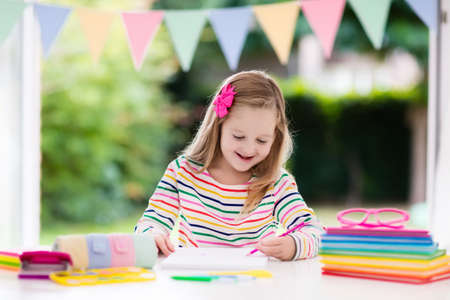 Child doing homework for school at white desk. Little girl with school supplies, abc books, drawing and painting tools and materials. Happy back to school student. Kid learning alphabet letters.
