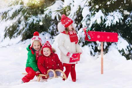 De gelukkige kinderen in gebreide rendierhoed en de brief van de sjaalholding aan Kerstman met Kerstmis stellen wenslijst bij rode brievenbus in sneeuw onder Kerstmisboom voor in de winterbos. Kinderen sturen post naar Noordpool.