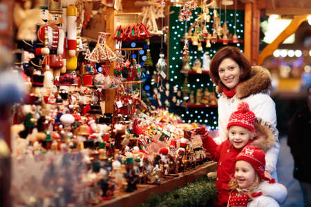 Moeder en kind in warme hoed kijken naar handgemaakte glazen kerstboomversieringen op traditionele Duitse Xmas straatmarkt. Familie met kind winkelen voor kerstcadeautjes op wintermarkt op besneeuwde dag.