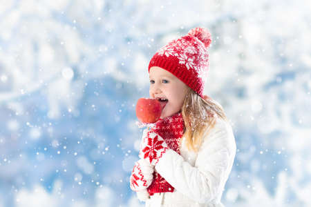 Child eating candy apple on winter fair. Kids eat toffee apples on Christmas market in snow. Outdoor fun on snowy day. Family vacation in Xmas season. Children play outdoors. Winter fashion for kids.