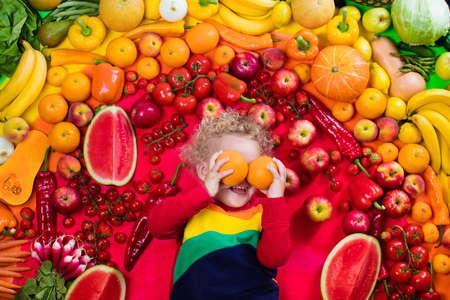 Neonato con varietà di frutta e verdura. Colorato arcobaleno di frutta fresca e verdura cruda. Bambino che mangia spuntino sano. nutrizione vegetariana per i bambini. Vitamine per i bambini. Vista dall'alto. Archivio Fotografico - 86416782