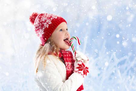 冬の見本市でリンゴ飴を食べる子。子供は雪のクリスマス ・ マーケットでリンゴを食べる。雪の日に屋外の楽しみ。クリスマス シーズンに家族で 写真素材