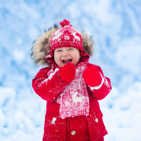 Baby playing with snow in winter. Little toddler boy in red jacket and Xmas reindeer knitted hat catching snowflakes in winter park on Christmas. Kids play in snowy forest. Children catch snow flakes