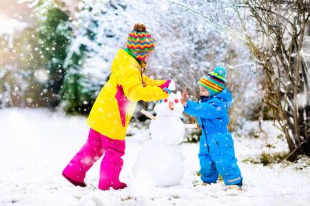 I bambini costruiscono pupazzo di neve. Bambini che costruiscono neve che gioca all'aperto all'aperto sulla giornata di sole invernale nevoso. Divertimento di famiglia all'aperto durante la vacanza di Natale. Ragazzo e ragazza giocare palla di neve. Abbigliamento invernale per bambino e bambino. Archivio Fotografico - 86472018