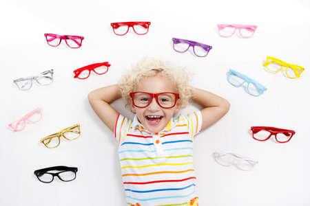 視力検査で子供。眼鏡店で眼鏡を選ぶ小さな子供。学校の子供のための視力測定。子供のための目の摩耗。眼の検査を行う医師。眼鏡のトップビュ