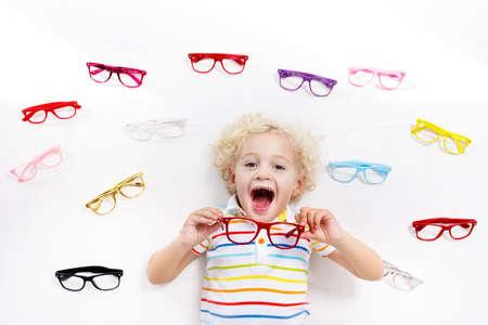 Kind bij gezichtsvermogen test. Weinig jong geitje die glazen selecteren bij opticienopslag. Gezichtsvermogenmeting voor schoolkinderen. Oogbescherming voor kinderen. Arts oogcontrole uitvoeren. Baby met bril bovenaanzicht. Stockfoto - 87015308