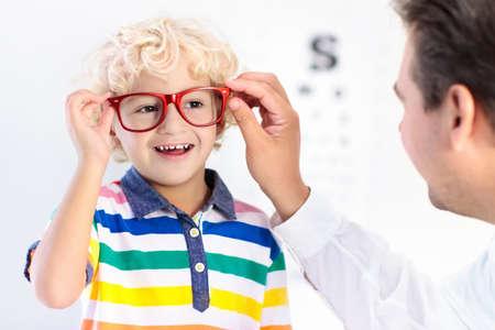 目の視力テストの子。小さな子供の眼鏡店でメガネを選択します。学校の子供たちの視力測定。子供の目の摩耗。目のチェックを実行する医師。メ 写真素材