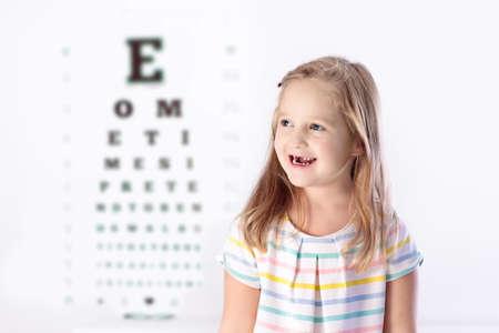 目の視力テストの子。小さな子供の眼鏡店でメガネを選択します。学校の子供たちの視力測定。子供の目の摩耗。目のチェックを実行する医師。手