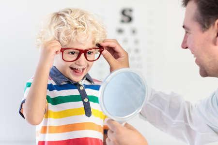 Niño en prueba de vista. Niño que selecciona los vidrios en la tienda óptica. Medición de la vista para niños de la escuela. Ojos para niños. Doctor que realiza la revisión visual. Niño con gafas en el cuadro de carta.