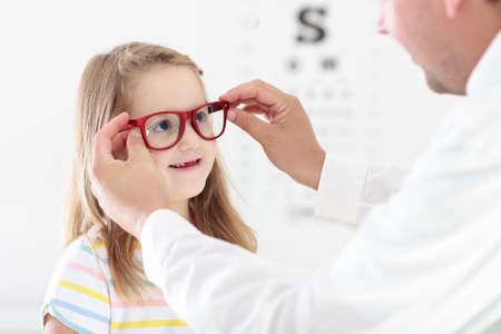 Kind bij gezichtsvermogen test. Weinig jong geitje die glazen selecteren bij opticienopslag. Gezichtsvermogenmeting voor schoolkinderen. Oogbescherming voor kinderen. Arts oogcontrole uitvoeren. Meisje met bril op de briefkaart. Stockfoto - 87015314