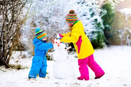 아이들은 눈사람을 만듭니다. 맑은 눈 덮인 겨울 날 야외에서 놀고 눈이 사람을 구축하는 아이. 크리스마스 휴가에 야외 가족 재미입니다. 소년과 소녀 스톡 콘텐츠