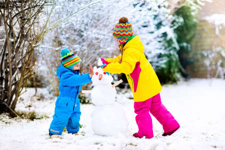 I bambini costruiscono pupazzo di neve. Bambini che costruiscono neve che gioca all'aperto all'aperto sulla giornata di sole invernale nevoso. Divertimento di famiglia all'aperto durante la vacanza di Natale. Ragazzo e ragazza giocare palla di neve. Abbigliamento invernale per bambino e bambino. Archivio Fotografico - 87073465