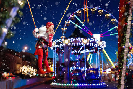 Child at Christmas amusement fair. Little girl at bungee jumping park. Kids jump at Xmas market in European city center on cold evening. Children outdoor winter fun. Ferris wheel and carousel for kid.