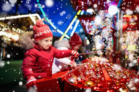 Kids at traditional Christmas fair. Children and Xmas market on snowy evening. Family shopping Christmas gifts and presents. Boy and girl play hook a bauble game. Winter fun. Advent time in Europe. Stock Photo - 87015318