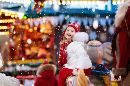 Happy little girl in warm jacket and red knitted Nordic hat and scarf riding carousel horse during family trip to traditional German Christmas market. Kids at Xmas outdoor fair on snowy winter day. Zdjęcie Seryjne - 87015322