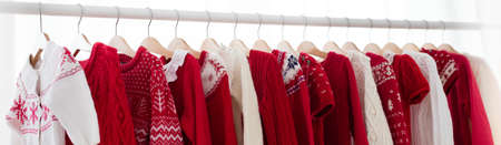 Clothes rack with red Christmas knit wear. Wardrobe with knitted winter jumper and dress. Xmas clothing collection. Christmas gifts shopping. Winter sale for children wear. Kids clothing shop. Фото со стока