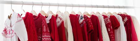 Ropas de ropa con rojo de punto de Navidad desgaste. Armario con jersey de punto y vestido de invierno. Colección de ropa de Navidad. Regalos de Navidad de compras. Venta de invierno para niños. Tienda de ropa para niños. Foto de archivo - 87015323