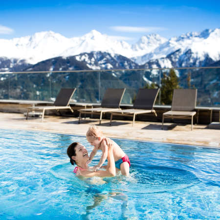 chairs: Mother and baby play in outdoor swimming pool of luxury spa alpine resort in Alps mountains, Austria. Winter and snow vacation for family with children. Kids in hot tub outdoors with mountain view.