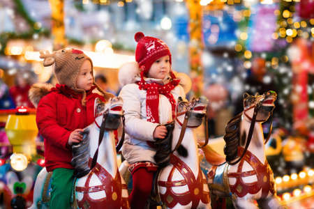 Happy little girl and boy in warm jacket and red knitted hat and scarf riding carousel horse during family trip to traditional German Christmas market. Kids at Xmas outdoor fair on snowy winter day. Stock Photo