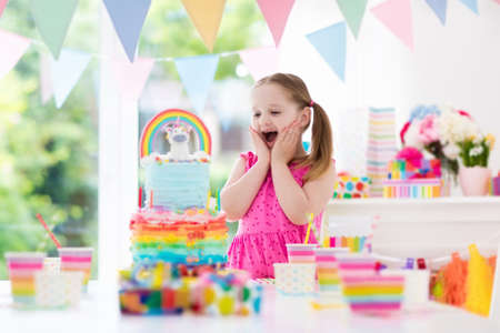 Kids birthday party with colorful pastel decoration and unicorn rainbow cake. Little girl with sweets, candy and fruit. Balloons and banner at festive decorated table for child or baby birthday party. Archivio Fotografico